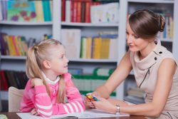 53061557 - child psychologist with a little girl, a child draws with colored pencils